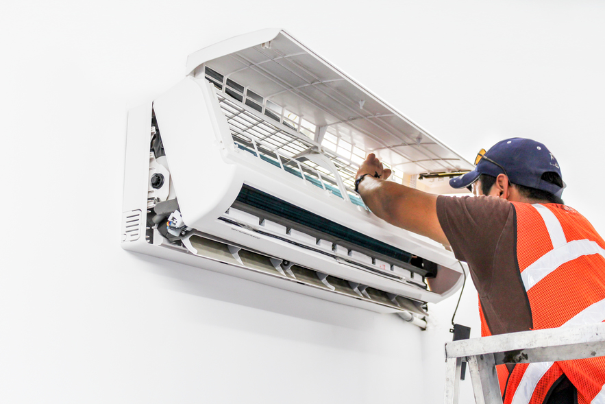 Young repairman fixing a ductless minisplit air conditioning system